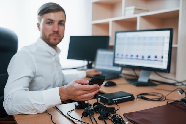 U kunt ons vertrouwen. polygraaf-examinator werkt op kantoor met de apparatuur van zijn leugendetector