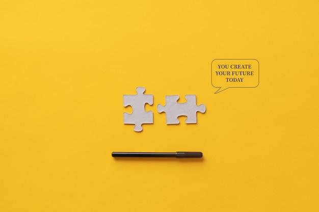 U maakt uw toekomstige vandaag-bericht geschreven op een gele achtergrond naast twee bijpassende puzzelstukjes en een zwarte stift.