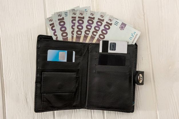 Uah, zwarte herenportemonnee zit vol met geld. uah geld van oekraïne 1000 en 500 bankbiljetten op bureau. geld en bespaar concept