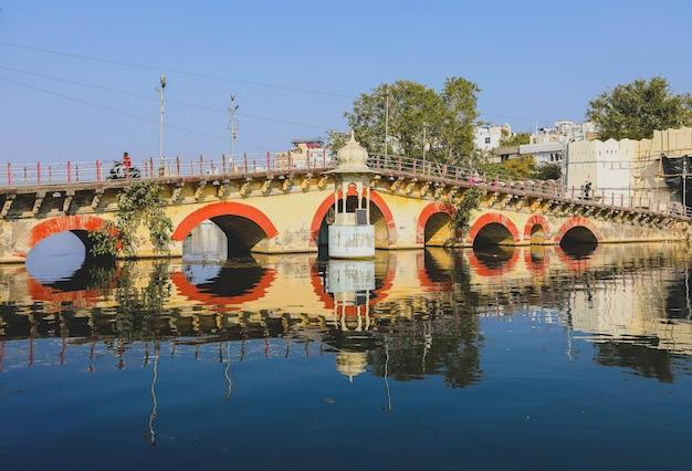 Udaipur, india - 19 januari 2020: boogbrug in de stad udaipur met zijn reflectie op water in een suumertime