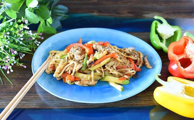 Udon met kip en groenten in sojasaus op een tafel