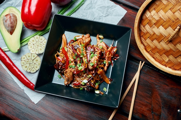Udon noedels met baby maïs, paprika, uien, wortelen en kalfsvlees gebakken op een wok met teriyaki saus in zwarte plaat op houten tafel. lekker aziatisch straatvoedsel
