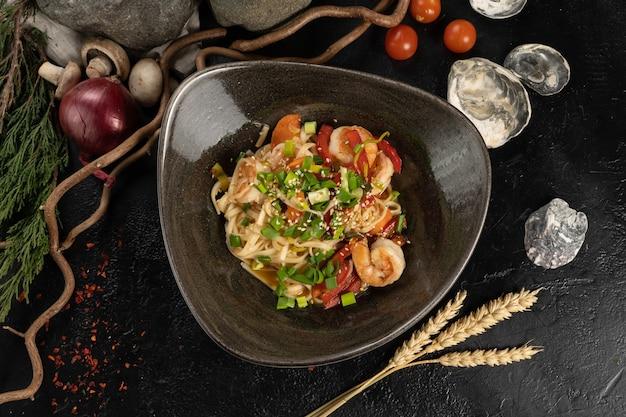 Udon noedels met garnalen en groene uien op een zwarte stenen keukentafel