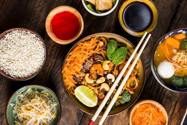 Udon-noedels uit de thaise keuken met sojasaus; rijst; bonen spruiten en soep op het bureau