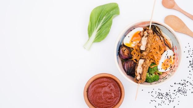 Udon-noedelskom met eieren; broccoli; sesamzaden en ui op witte achtergrond