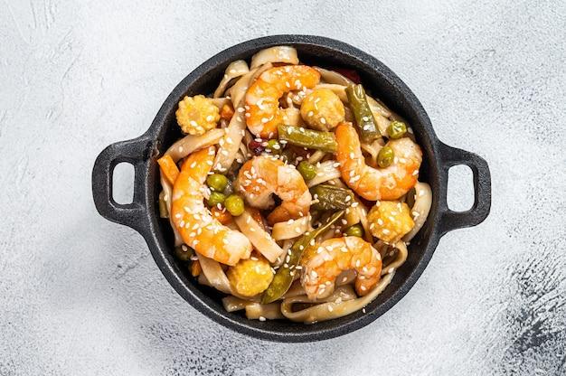 Udon roerbak noedels met garnalen garnalen in een pan.