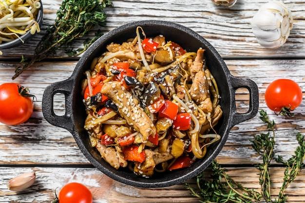 Udon roerbaknoedels met kip en groenten in een pan op wit. bovenaanzicht