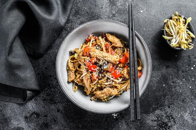 Udon roerbaknoedels met kippenvlees en sesam op zwart