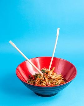 Udon roergebakken noedels met kip paprika wortel lente-ui sojasaus en sesam in een kom met stokjes