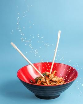 Udon roergebakken noedels met kip paprika wortel sojasaus lente-ui en sesam in een kom met stokjes