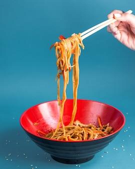 Udon roergebakken noedels met paprika wortel lente ui sojasaus en sesam in een kom