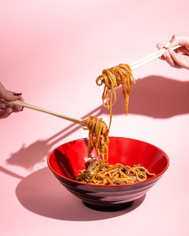 Udon roergebakken noedels met vlees, paprika, lente-ui, sojasaus en sesam in een kom