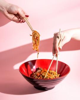 Udon roergebakken noedels met vlees, paprika, sojasaus, lente-ui en sesam in een kom