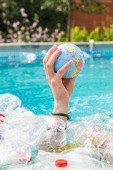 Ufa, rusland - 25 juli 2019: probleem van afval, plastic recycling, vervuiling en milieuconcept - plastic afvalvervuiling in het watermilieu, earth globe drijft in de prullenbak.