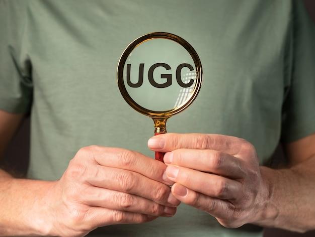 Ugs of user-generated content acroniem voor sociale media door vergrootglas in volwassen mannelijke handen.