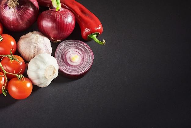 Ui en knoflook en hete pepers en tomaten geïsoleerd op een zwarte.