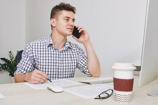 Ui-ontwerper die correcties in het ontwerp aanbrengt tijdens een telefoongesprek met de klant