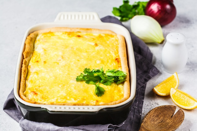 Ui taart met kaas en kruiden in zwarte ovenschaal.