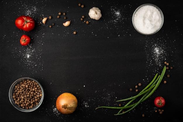 Ui, tomaten, knoflook, aardappel en zwarte peper op zwarte achtergrond.
