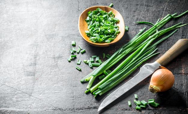 Uien en groene uien. op donkere rustieke tafel