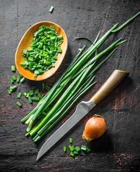 Uien en groene uien op rustieke tafel