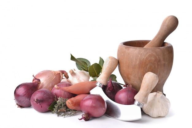 Uien, knoflook en sjalotten met een handmatige hakmolen en stamper op wit