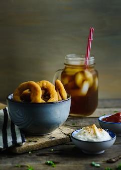 Uienringen, sauzen en frisdrank in een houten tafel