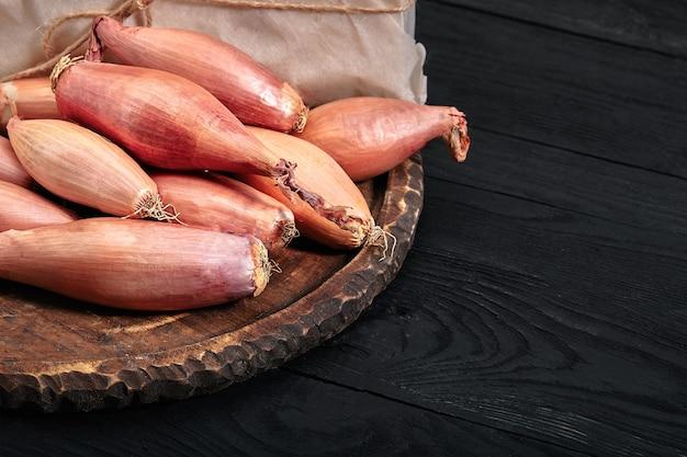 Uiensjalot op een zwarte, donkere achtergrond groenten eten en gezond eten sjalotten eten als aanvulling op verschillende gerechten, diversificatie van voedsel