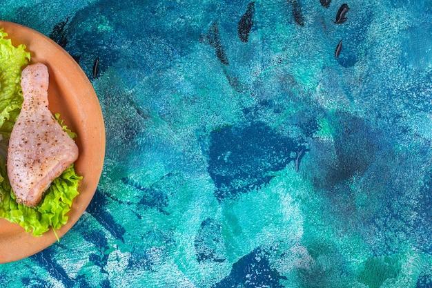 Uienslabladeren en kippendrumstick op een kleiplaat