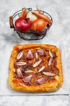Uientaartgalette in franse stijl met bladerdeeg en verschillende uiensjalot, rode, witte, gele uien, bovenaanzicht