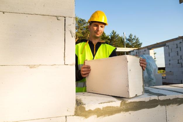 Uilder houdt een blok cellenbeton in zijn handen - het metselwerk van de muren van het huis.