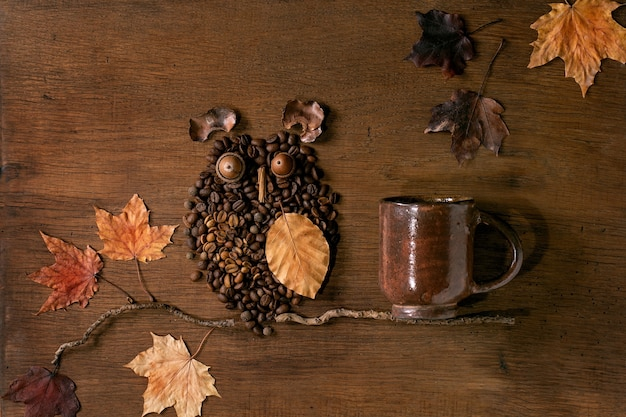 Uilvorm van koffiebonen en kruiden. uil zit op de tak met koffiekopje en herfstbladeren over houten achtergrond. grappig herfstmysterie koffieconcept