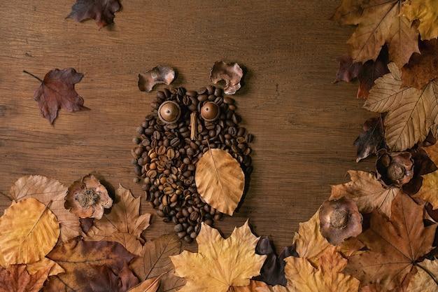 Uilvorm van koffiebonen en kruiden. uil zit op de tak met koffiekopje en herfstbladeren over houten achtergrond. grappig mysterie koffie concept