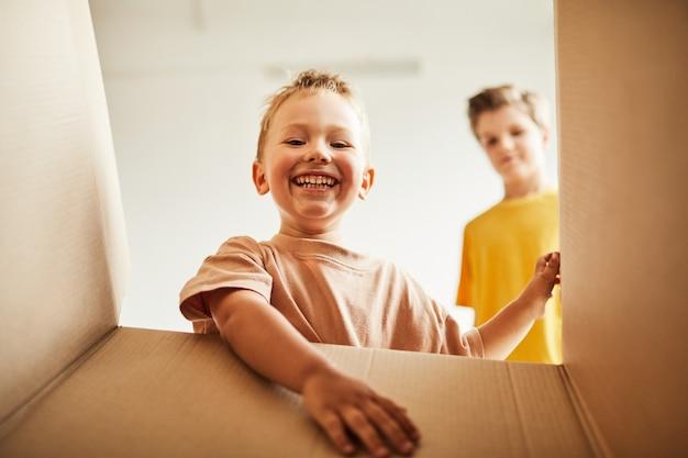 Uit de doosopname van twee jongens die uitpakken terwijl het gezin verhuist naar de kopieerruimte van een nieuw huis