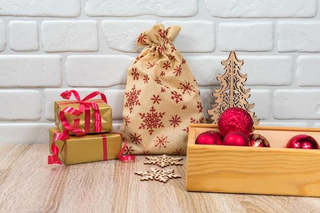 Uit hout gesneden kerstboom, zak met rode sneeuwvlokken en ballen in een houten kist.