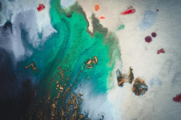 Uitbarstingen van veelkleurige verf en vermengd wit papier. getekende spatten van verven van verschillende kleuren op witte ondergrond. blauwe, gele, rode, groene kleur. sproeien sproeien stroom lekstroom mengen
