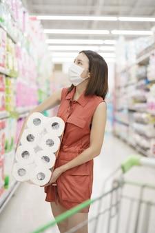Uitbraak van covid-19. vrouw in medisch beschermend maskerpaniek het kopen papieren zakdoekje. angst voor coronavirus.