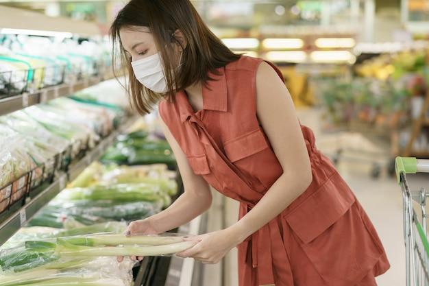 Uitbraak van covid-19. vrouw in medisch beschermend maskerpaniek het kopen voedsel. angst voor coronavirus.