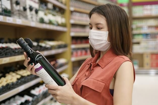 Uitbraak van covid-19. vrouw in medische beschermende maskerpaniek het kopen wijn. angst voor coronavirus.