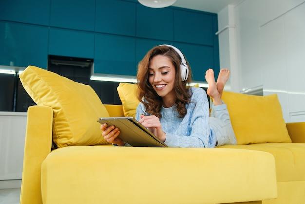 Uitbundige gelukkige vrouw gebruikt tablet-pc terwijl ze op de comfortabele gele bank ligt en luistert naar muziek met oortelefoons.