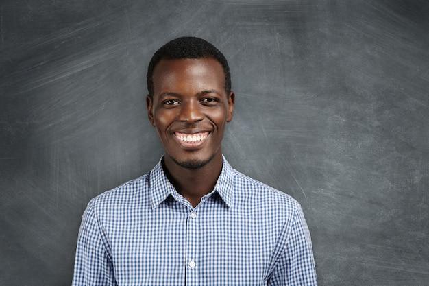 Uitdrukkingen, emoties en gevoelens van menselijke gezichten. portret van vrolijke afrikaanse werknemer lachend met zijn witte tanden, blij met grote promotie en carrièregroei. succes en prestaties.