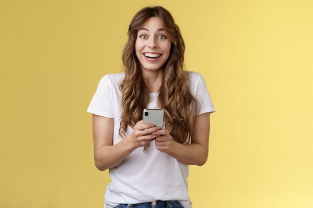 Uiterst blij enthousiast verrast blij mooi vrouwelijk meisje ontvangt aangenaam ontroerend bericht online houd smartphone glimlachend breed kijk camera vrolijk geamuseerd gele achtergrond