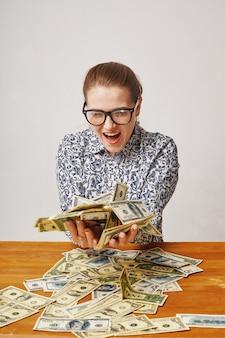 Uiterst gelukkige jonge vrouw met dollars in haar handen