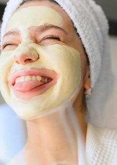 Uiterst gelukkige vrouw met gezichtsmasker op