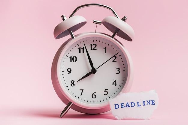 Uiterste termijnbericht op gescheurd document stuk dichtbij de wekker tegen roze achtergrond