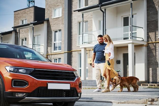 Uitgaan van het gebouw. mooie paar hebben een wandeling samen met hond buiten in de buurt van de auto.