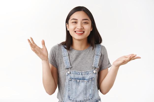 Uitgaand vriendelijk aziatisch schattig meisje acne gevoelig huid vrolijk voelen positief vermaakt emoties gebaren beweging handen in het algemeen veel plezier speels stemming staand witte muur