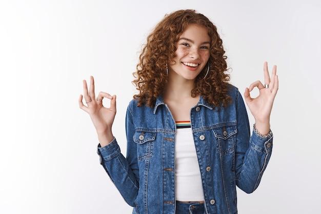 Uitgaand vriendelijk blij lachend roodharig meisje met sproeten puistjes dragen spijkerjasje lachen plezier hebben gevoel geweldig laten zien oke ok cool gebaar blij goed perfect resultaat, witte achtergrond