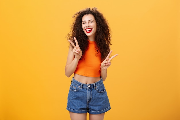 Uitgaande vriendelijk ogende aantrekkelijke jonge vrouw met krullend kapsel in bijgesneden top en korte broek met vredes- of overwinningstekens met beide handen en vrolijk lachend met plezier over oranje achtergrond.