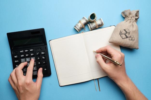 Uitgaven en inkomsten planningsconcept met hand en dagboek